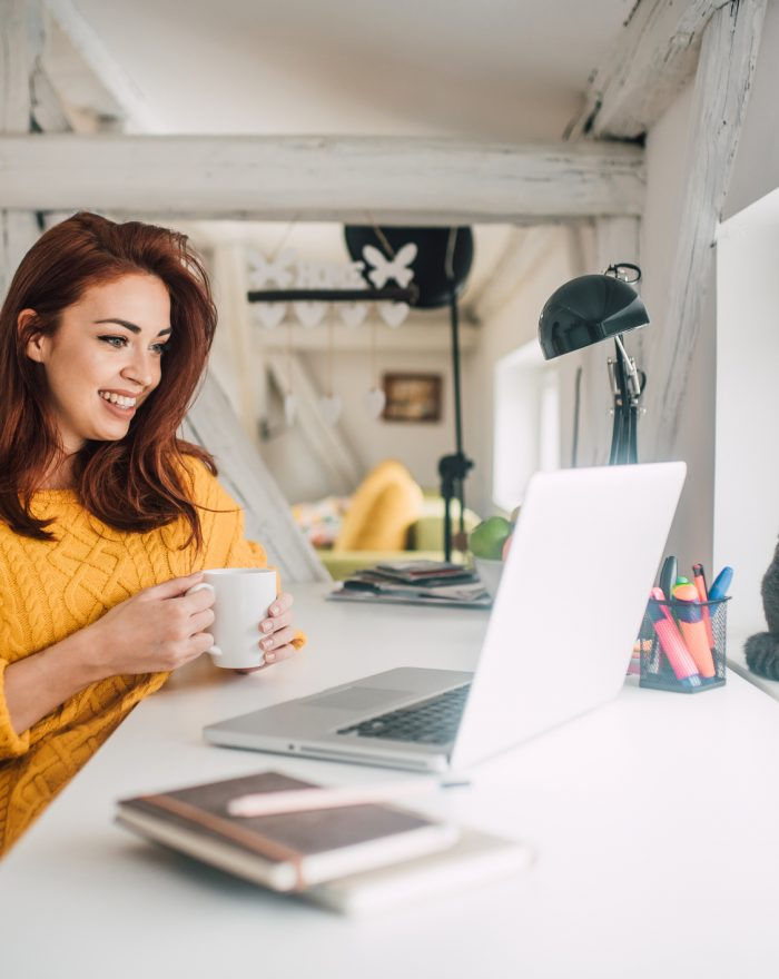 Smiling young redhead holding a cup of coffee while working on her laptop in her home office with a cat sitting in a window